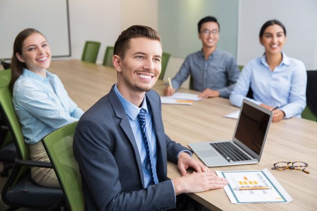 Cheerful young Caucasian businessman sitting at conference or seminar in boardroom with multiethnic business people, looking at camera and smiling